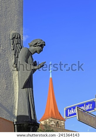 Angel statue on the wall and cathedral with road signs in Nuremberg, Germany  - stock photo