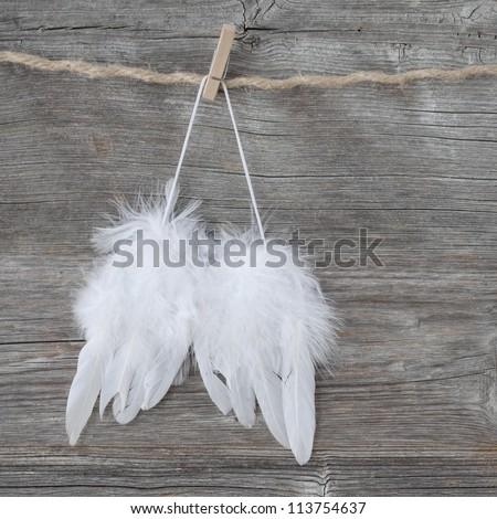 Angel wings on grey wooden background - stock photo