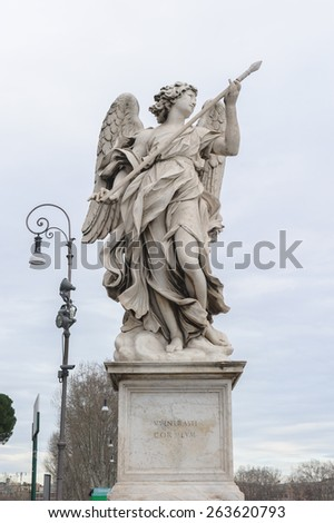 Angel with the Lance is a statue on the Ponte Sant'Angelo in Rome, Italy. Ponte Sant'Angelo is a bridge in front of the Castel Sant'Angelo. - stock photo