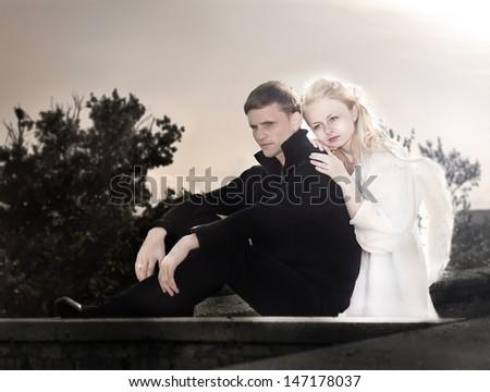 Angel woman embraces  upset unfortunate man - stock photo