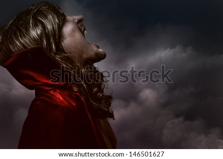Anger, Elegant Young Vampire with black coat and long hair, nude - stock photo