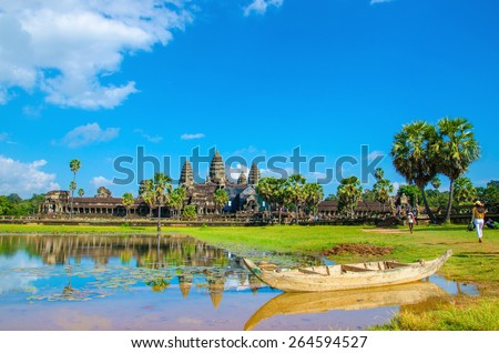 Angkor Wat with old boat seen across the lake, Siem Reap, Cambodia - stock photo