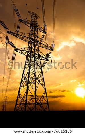 Angle shot of power lines against sunset in the background - stock photo