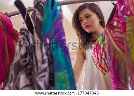 Angle view of a shop woman looking through the new fashion collection on the foreground  - stock photo