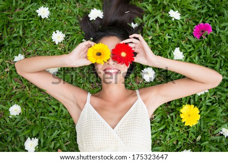 Angle view of a woman holding gerbera flowers on her eyes while lying on the grass - stock photo