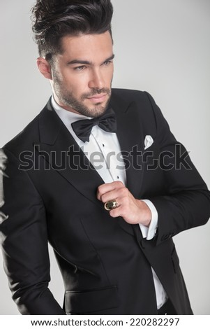 Angle view of an elegant young man ajusting his tuxedo, looking away from the camera. - stock photo