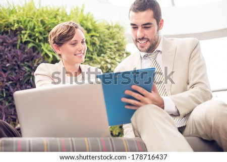 Angle view of cheerful businesspeople cooperating at a cafe on the foreground - stock photo