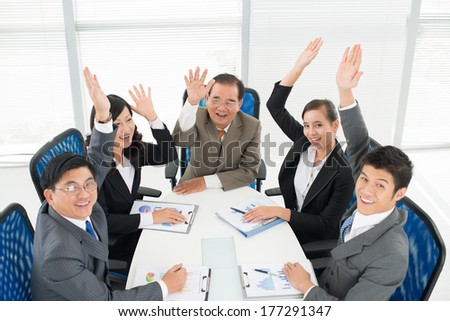 Angle view of cheerful businesspeople with raised hands in the office  - stock photo