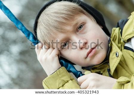 Angled close up view on serious blond male child in coat hanging on to chain on swing outdoors - stock photo