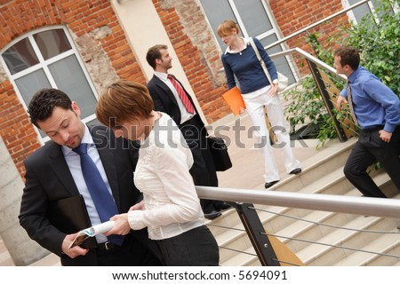 Angled shot of five people dressed in business and casual business attire, in various activities. - stock photo