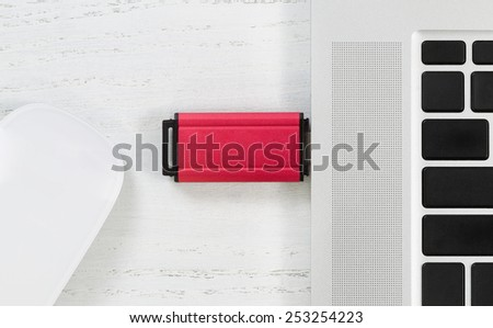Angled top view image of red color thumb drive in laptop USB port and mouse on white desktop. Security concept with vulnerability access to laptop.    - stock photo