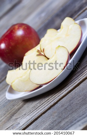 Angled vertical photo of fresh apple slices, on white plate, with whole apple and rustic wood in background   - stock photo