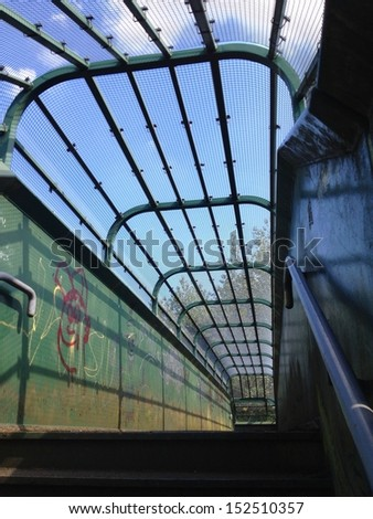 Angled view of enclosed walkway over railroad tracks. - stock photo