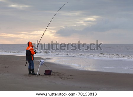 Angler on an deserted beach at sunset - stock photo