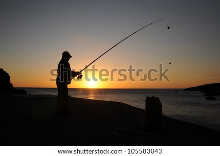 Angler's shadow in evening sun - stock photo