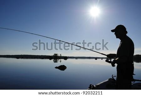 Angler's shadow in morning sun - stock photo