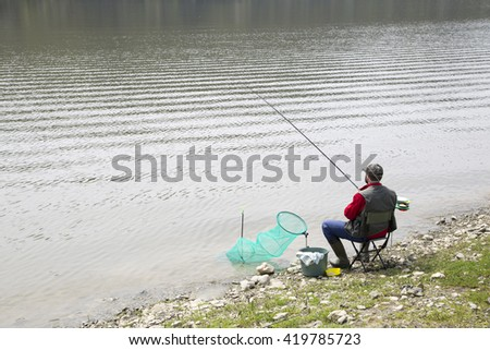 Angler Sitting On The River Coast And Patiently Waiting For Fish To Take A Bait - stock photo