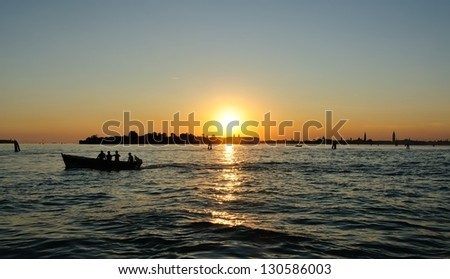 anglers in boat fishing at sunset - stock photo