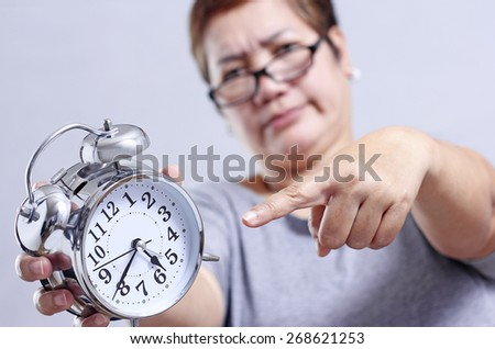 Angry adult woman pointing to a table clock. - stock photo
