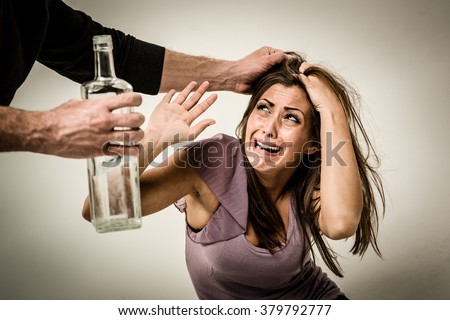 Angry aggressive drunk husband is physically abusing his wife.  - stock photo