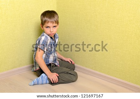 Angry and sad boy sitting in corner - stock photo