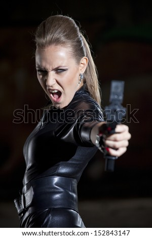 angry and screaming woman in leather suit aiming with a gun - stock photo