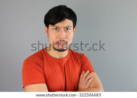 Angry Asian man in Red T-shirt. - stock photo