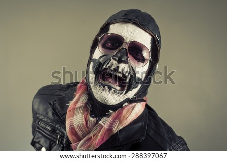 Angry aviator with face painted as human skull - stock photo