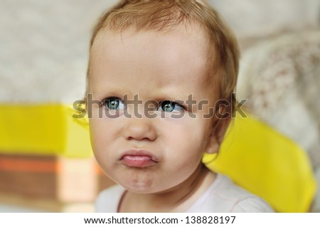 angry baby girl making face - stock photo