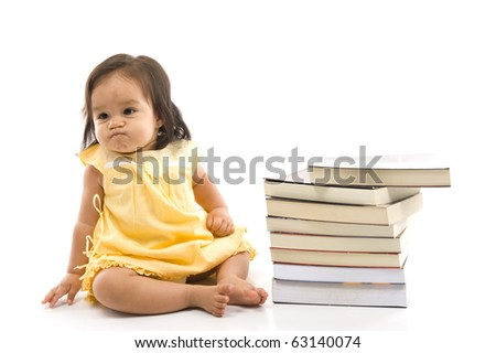 Angry Baby with a pile of books . - stock photo