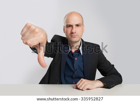 angry bald businessman showing his thumb down. Studio shot - stock photo