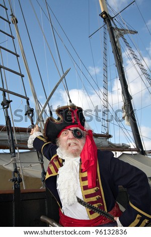 Angry bearded pirate captain in colorful traditional costume stands on board ship and waves his sword. Schooner rigging and blue sky in background, vertical layout. - stock photo
