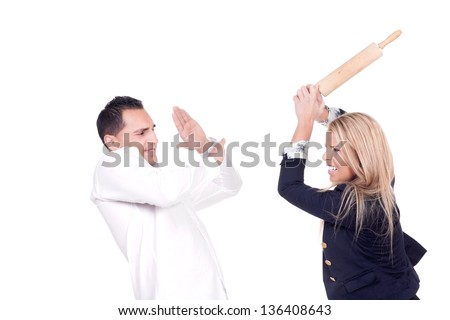 Angry blond woman hitting her partner with a cooking roller in a fight - stock photo