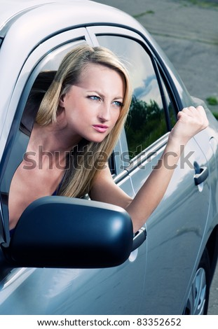 Angry blond young woman sitting in a car - stock photo