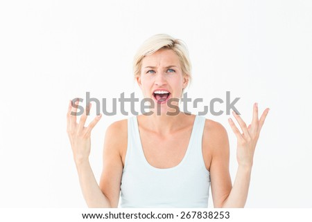 Angry blonde yelling with hands up on white background - stock photo