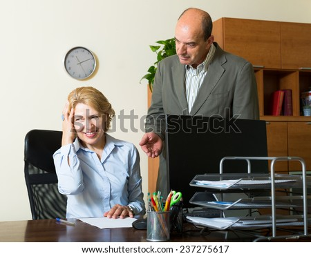 Angry boss screaming at careless aged secretary in office - stock photo