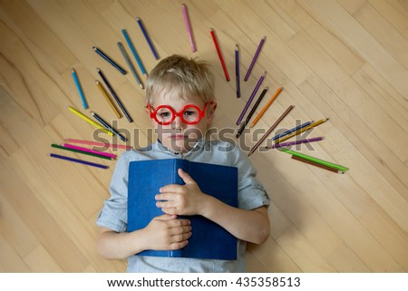 Angry boy in red with glasses hugging blue book lying on the floor around colored pencils - stock photo