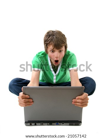 Angry boy looking at laptop computer - stock photo