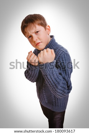 angry boy teenager fight  clenched his fists isolated on white background gray - stock photo