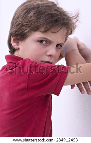 Angry boy with his arms resting on the wall - stock photo