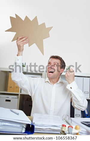 Angry business man ranting with jagged speech balloon in the office - stock photo