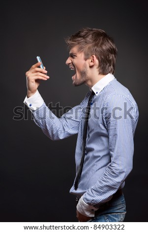 Angry business man screaming on phone over black background - stock photo