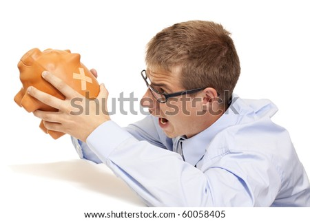 Angry business man shaking the piggy bank - stock photo