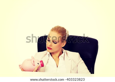 Angry business woman looking for her piggybank and sitting behind the desk - stock photo