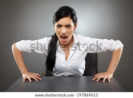 Angry business woman shouting with her hands on the desk - stock photo