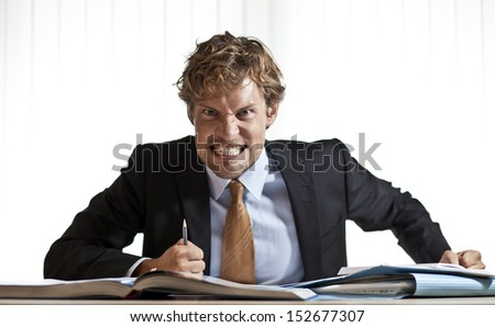 Angry businessman at desk grinding his teeth in anger - stock photo