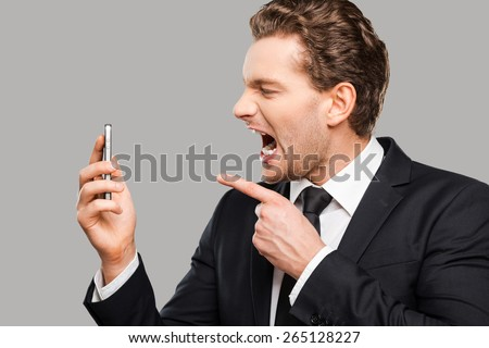Angry businessman. Furious young man in formalwear holding mobile phone and shouting at it while standing against grey background  - stock photo