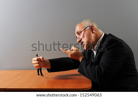 angry businessman holding in his fist small man - stock photo
