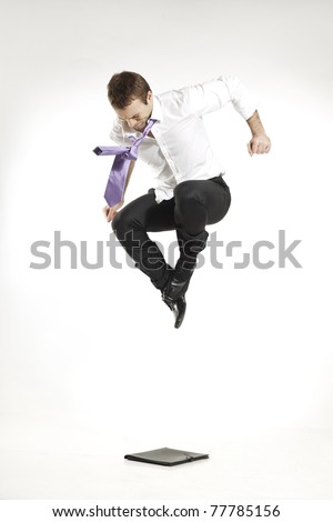 angry businessman jumping and stomping on a business portfolio - stock photo