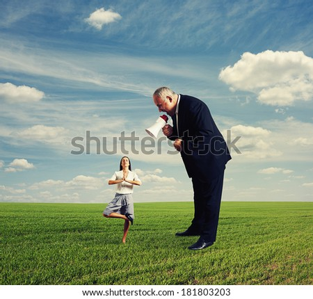 angry businessman screaming at calm small businesswoman - stock photo